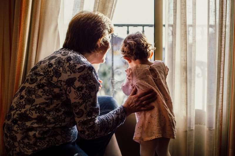 Grandmother with little girl looking out the window.